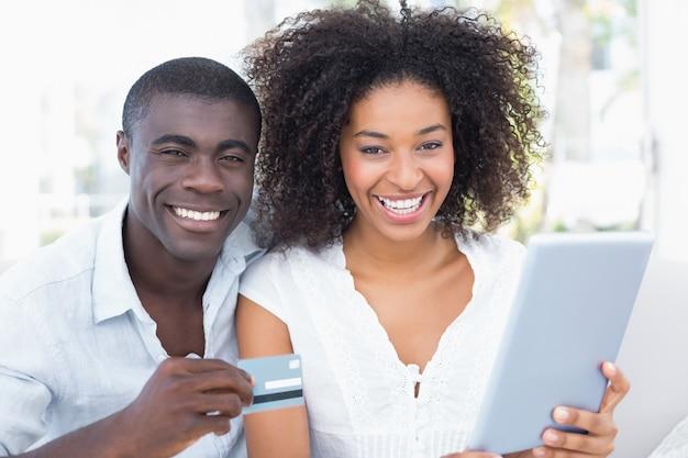Coppie attraenti facendo uso della compressa insieme sul sofà per acquistare online