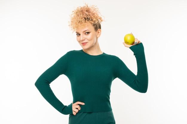 Attraente ragazza bionda riccia con una bella figura tiene una mela in mano su uno sfondo bianco.