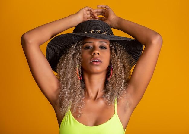 Ragazza attraente capelli ricci in un bikini verde brillante, cappello, bocca emotivamente aperta su una parete giallo brillante con un corpo perfetto. isolato.