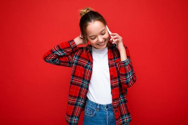 Attraente carino positivo giovane donna bionda in piedi isolato su red