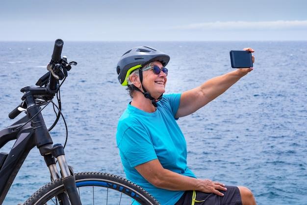 Attraente donna ciclista che riposa in mare sulla scogliera dopo l'attività con la sua bici elettrica. seduto usando il cellulare per un selfie