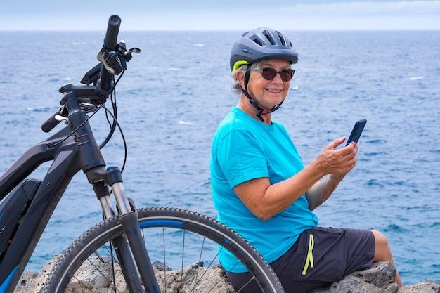 Attraente donna ciclista che riposa in mare sulla scogliera dopo l'attività con la sua bici elettrica. seduto usando il cellulare