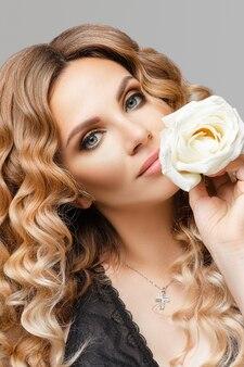Attraente modello biondo scuro con capelli mossi e trucco professionale che tiene un fragile bocciolo di rosa bianca in primo piano.