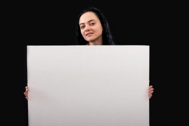 Attraente donna dai capelli scuri in un maglione grigio con un poster bianco in bianco, isolato su uno sfondo scuro