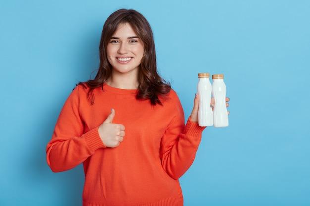 Attraente donna dai capelli scuri che tiene due bottiglie di latte, che guarda l'obbiettivo con un sorriso, mostrando il pollice in su, isolato sulla parete blu, femmina per uno stile di vita sano, prodotto biologico.