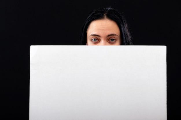 Attraente donna dai capelli scuri guardando oltre poster bianco bianco, isolato su sfondo scuro