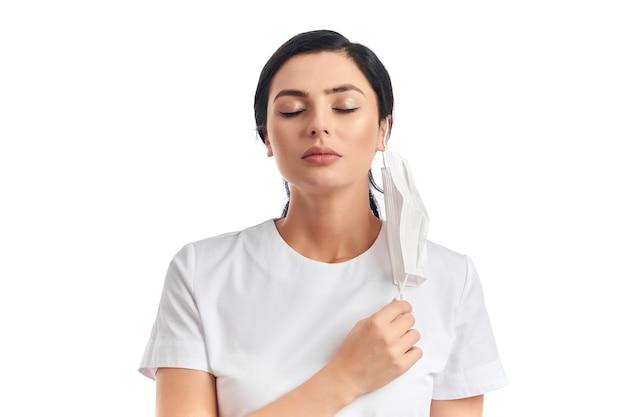 Attraente donna dai capelli scuri in piedi sul bianco con gli occhi chiusi e che si toglie la maschera medica per fare un respiro profondo