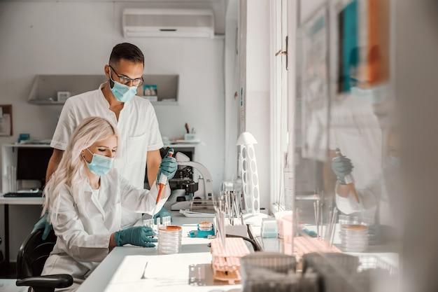 Attraente assistente di laboratorio femminile bionda dedicata con maschera facciale e guanti di gomma che fa ricerche per la cura per il virus corona.