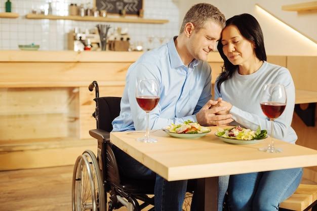 Attraente uomo handicappato felice e una donna dai capelli scuri piuttosto gioiosa che si siede con gli occhi chiusi e si tengono per mano mentre si cena romantica