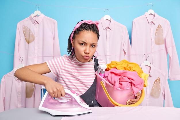 Attraente casalinga scontenta tiene il secchio pieno di biancheria impegnata a stirare e fare lavori domestici