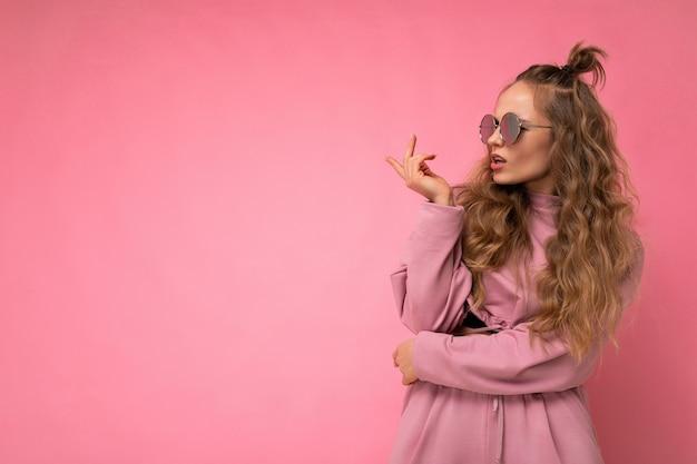 Attraente insoddisfatto chiedendo giovane donna bionda che indossa abiti alla moda di tutti i giorni e occhiali da sole moderni isolati sulla parete di superficie colorata che osserva al lato e che ha dubbi