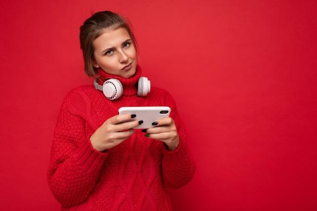Attraente giovane donna insoddisfatta del brunet che indossa un maglione rosso isolato su sfondo rosso muro