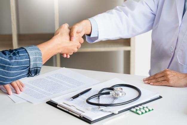 Medico e paziente attraenti che stringono le mani per incoraggiamento ed empatia, sanità e assistenza, concetto medico.