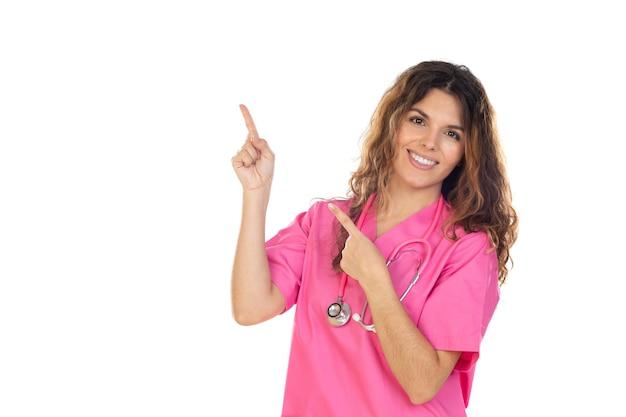 Attraente medico che indossa una divisa rosa isolata su uno sfondo bianco Foto Premium