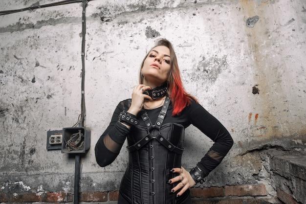 Attraente donna dominante con piercing e capelli luminosi in un corsetto nero, con imbracature in pelle e braccialetti in posa