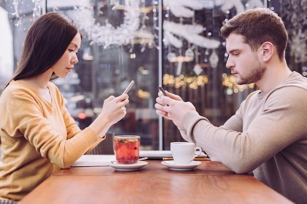 Attraente coppia piacevole seria seduta tenendo i telefoni e guardando gli schermi