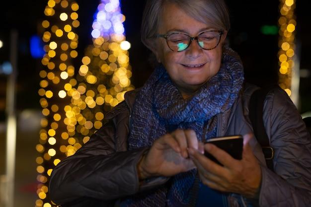 Attraente signora anziana scrive un messaggio con il cellulare all'aperto di notte vicino a un albero di natale illuminato