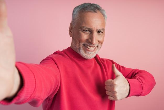 Uomo attraente e anziano che prende un selfie, pollice in su