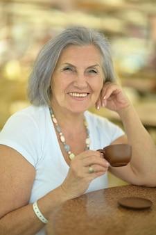 Attraente donna anziana con una tazza di caffè