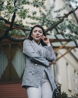 Modello elegante attraente che posa in giacca nella città di primavera