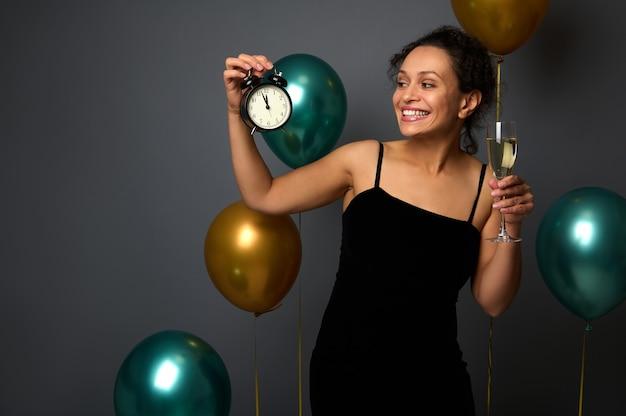 Attraente donna elegante in abito da sera nero isolato su sfondo grigio con palloncini verdi dorati, con in mano un flauto di spumante e guardando la sveglia, pronta per la festa di capodanno