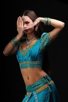 Attraente ragazza europea in abito tradizionale blu indiano che mostra il movimento di danza nazionale. gioielli su testa, mani e collo. isolato su sfondo scuro