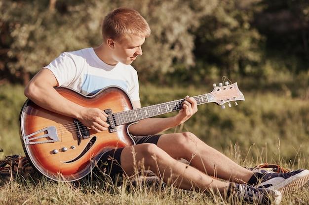 L'adolescente maschio europeo attraente si siede sull'erba, suona la chitarra acustica, durante il giorno d'estate, esercita la nuova canzone, canta, gode l'atmosfera calma all'esterno. concetto di persone e divertimento