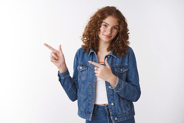 Attraente europea giovane rossa ragazza dai capelli ricci lentiggini brufoli sorridente ampiamente invitante amico vegan cafe puntando l'indice sinistro chiedendo prova sorridendo gioiosamente sfondo bianco