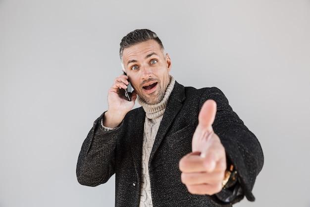Attraente uomo eccitato che indossa un cappotto in piedi isolato su un muro grigio, parla al telefono cellulare, punta il dito davanti