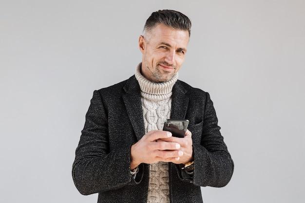 Attraente uomo eccitato che indossa un cappotto in piedi isolato su un muro grigio, usando il telefono cellulare