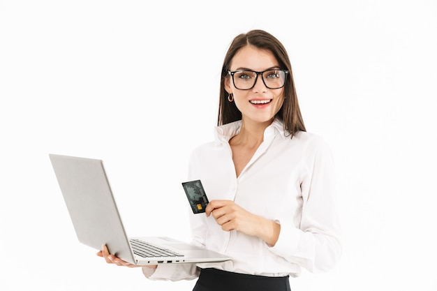 Attraente giovane donna d'affari eccitata in piedi isolata su un muro bianco, con in mano un computer portatile, mostrando la carta di credito