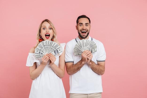 Attraente giovane coppia eccitata che sta insieme isolata sopra il rosa, mostrando banconote in denaro