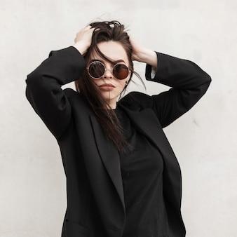 Attraente modella abbastanza giovane donna in elegante abbigliamento casual giovanile in occhiali da sole alla moda raddrizza l'acconciatura vicino al muro bianco vintage in città. ritratto di strada splendida ragazza sexy all'aperto.