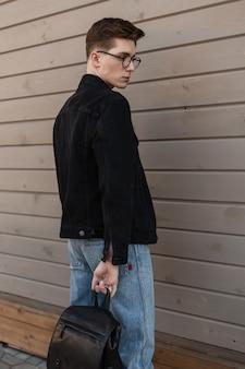 Attraente giovane alla moda con gli occhiali con l'acconciatura in eleganti vestiti casual in denim