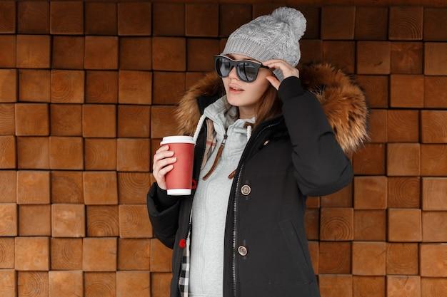 Pantaloni a vita bassa alla moda attraente della giovane donna in occhiali da sole in un cappello lavorato a maglia in una giacca invernale con un cappuccio di pelliccia sta all'aperto e tiene in mano una tazza rossa con caffè caldo gustoso. bella ragazza americana.