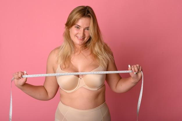 Attraente ragazza grassa con nastro di misurazione sul rosa