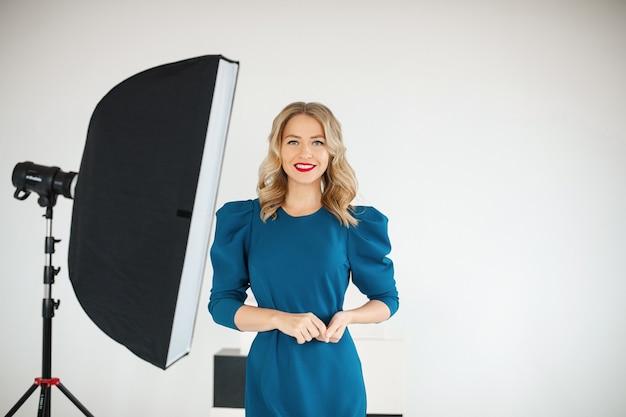 Attraente donna in abito blu con capelli biondi posa per la fotocamera in studio