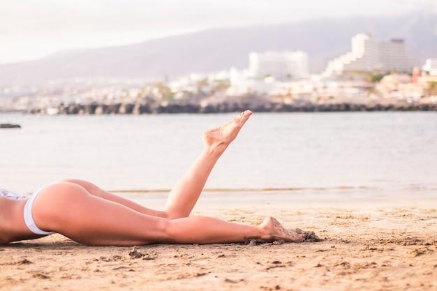 Corpo femminile attraente e belle gambe di donna si rilassano e si sdraiano sulla spiaggia prendendo il sole sulla sabbia. riva e oceano per il concetto di vacanza estiva di vacanza. ragazze in viaggio