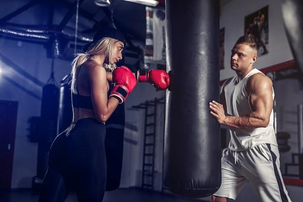 Attraente pugile femminile che si allena colpendo il sacco da boxe
