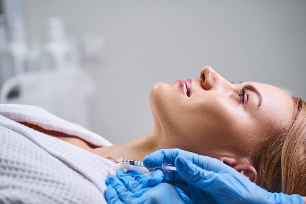 La donna attraente è sdraiata sul divano nella stanza di cosmetologia mentre il professionista le fa un'iniezione nel collo