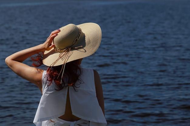 Attraente persona di sesso femminile in abito bianco con cappello glamour all'aperto sulla riva del fiume, vista posteriore, acqua blu profonda sullo sfondo. copia.