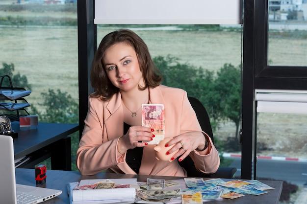 Una donna attraente mette una banconota da 50 sterline nel salvadanaio rosa per risparmiare denaro seduto in ufficio. dollari, sterline inglesi e nuove banconote di shekel sul tavolo. donna d'affari con i capelli mossi