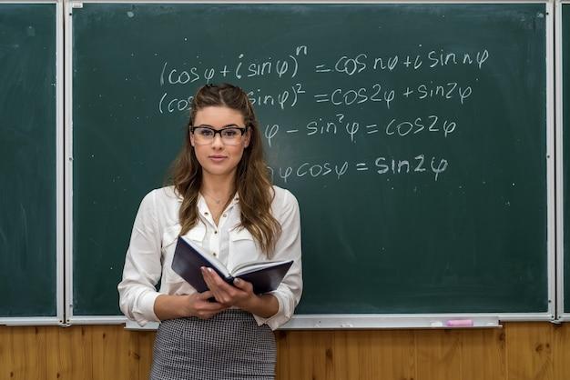 Insegnante femminile attraente in vetri vicino alla lavagna con i calcoli di matematica. di nuovo a scuola