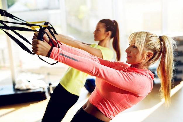 Femmine attraenti allenandovi in palestra.