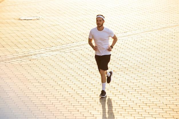 Uomo attraente in forma che corre in città al tramonto