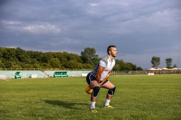 Calciatore in forma attraente in piedi sul campo e campana oscillante.