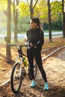 Attraente sportiva in forma con una bicicletta al parco, acqua potabile da una bottiglia