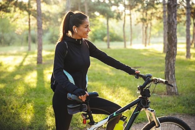 Attraente sportiva in forma con una bicicletta al parco