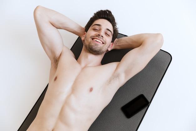 Attraente giovane sportivo senza camicia in forma sdraiato su un tappetino fitness con telefono cellulare a schermo vuoto, isolato, a riposo
