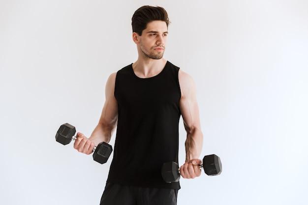 Attraente giovane sportivo in forma in piedi isolato su un muro bianco, che si esercita con i manubri